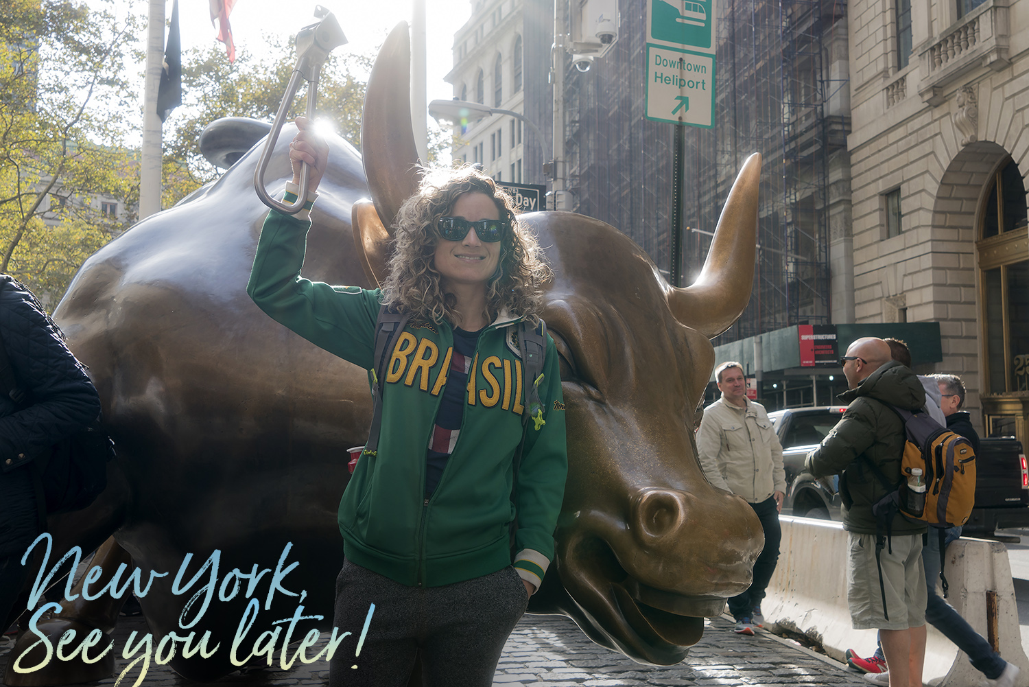 Emille holding the Subway Handle in front of the Charging Bull in NYC's Financial District