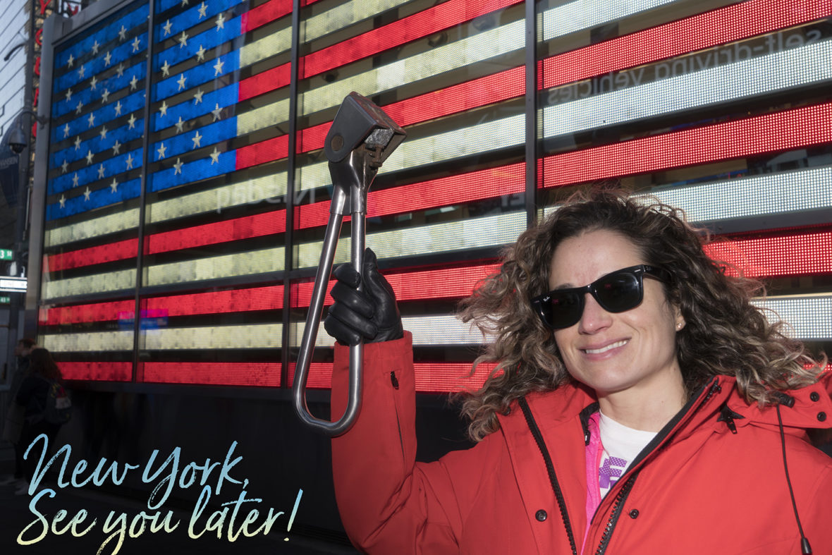 Emille holding the Subway Handle in front of the American Flag in Times Square, NYC