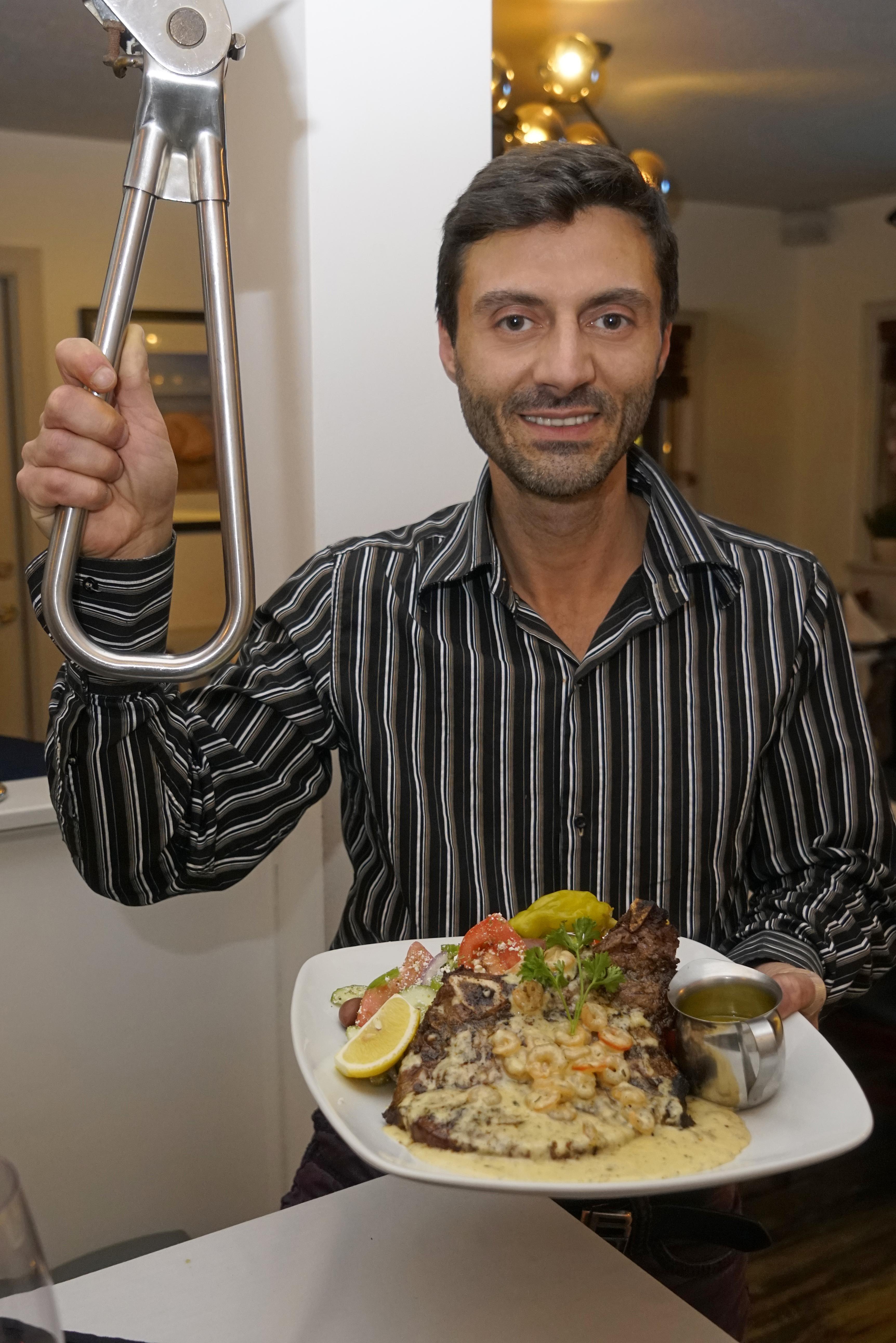 Yianni holding the subway handle and the beautiful 20 Ounces, AAA bone-in ribeye steak