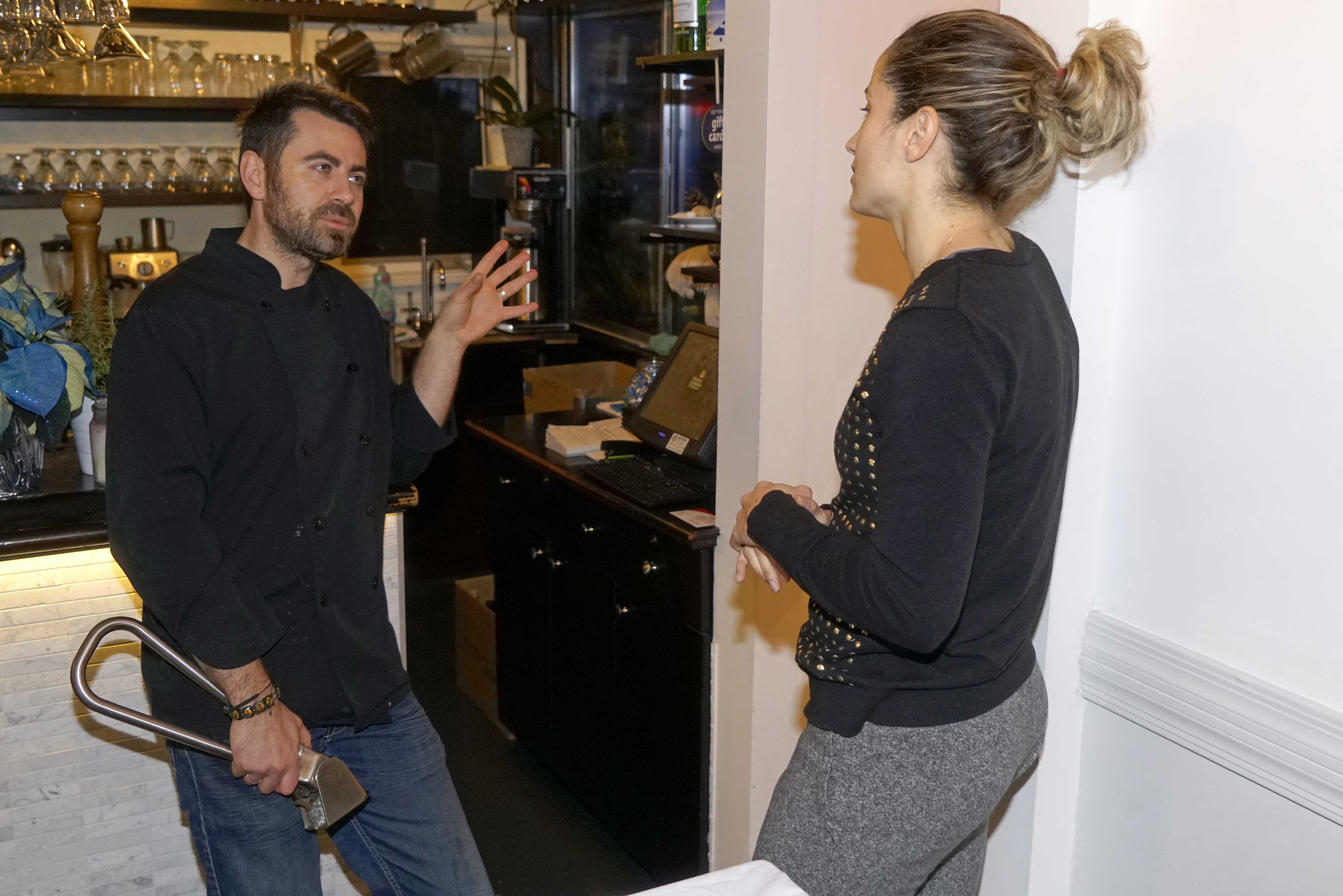 Nikolas of the partners of My Greek Place holding the subway handle while having a conversation with Emille