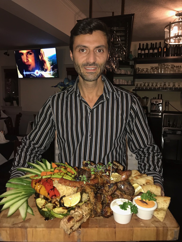 Yianni the owner of My Greek Place holding a beautiful platter of various meats