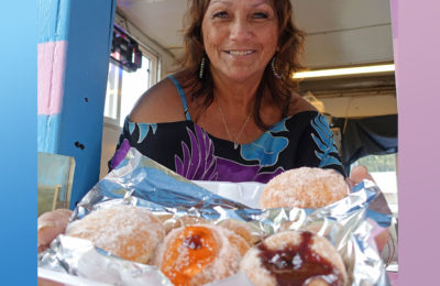 The owner holding delicious, hot malasadas in the Hot Malasadas Truck on The Big Island of Hawaii